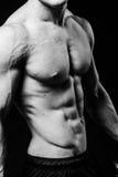 Muskulöser sexy Torso des jungen sportlichen Mannes mit perfekter ABS schließen oben Schwarzweiss lokalisiert auf schwarzem Hinte Lizenzfreie Stockbilder