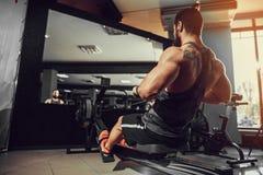 Muskulöser Sitzmann, der Rudermaschine an der Turnhalle verwendet Stockbilder