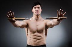 Muskulöser starker Mann mit nunchucks Stockfotos