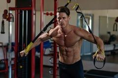 Muskulöses Bodybuildertraining des Athleten auf Simulator in der Turnhalle Stockfoto