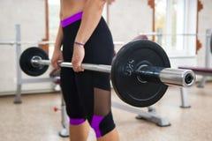 Muskulöses Eignungsmädchen, das schwere deadlift Übung in der Turnhalle tut Stockfoto