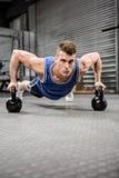 Muskulöst göra för man skjuter upp med kettlebells Royaltyfri Foto