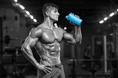 Muskulöst mandricksvatten i idrottshallen, format buk- Stark manlig naken torsoabs som utarbetar arkivbild
