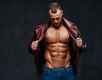 Muskulöst manligt iklätt ett omslag och jeans Royaltyfria Foton