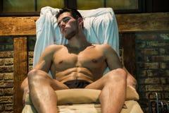 Muskulöst mansammanträde på schäslong med ögon stängde sig royaltyfria foton