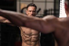 Muskulöst posera för konditionmodell som är shirtless i idrottshallen fotografering för bildbyråer