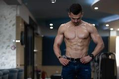Muskul?s kroppsbyggare i jeans som b?jer muskler fotografering för bildbyråer