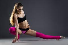 Muskulös attraktiv konditionkvinna som värmer upp i studion på grå bakgrund Royaltyfri Fotografi