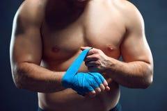 Muskulös boxare som förbinder hans händer på grå färger Royaltyfria Bilder
