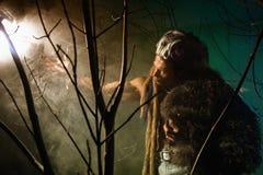 Muskulös man med hud och dreadlocks som ser ett ljust ljus Fotografering för Bildbyråer