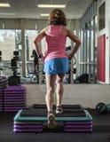 Muskulöse Frau, die Stepp-Aerobic tut Stockbilder