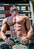 Muskulöser Bodybuilder, der auf hölzerne Treppe in der Sonne legt Stockbild