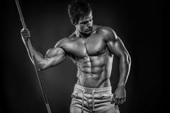 Muskulöser Bodybuilderkerl, der die Aufstellung mit Dummköpfen über Schwarzem tut Stockfoto
