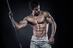 Muskulöser Bodybuilderkerl, der die Aufstellung mit Dummköpfen tut Stockfotos