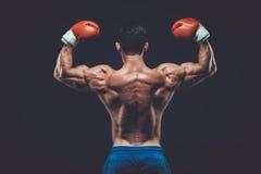 Muskulöser Boxer im Studioschießen, auf schwarzem Hintergrund Lizenzfreie Stockfotos