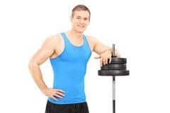Muskulöser Mann, der auf einem Barbell sich lehnt Stockbild