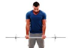 Muskulöser Mann, der Übungen mit Barbell tut Stockfotos