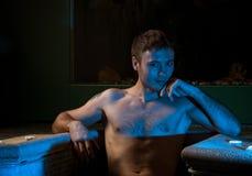 Muskulöser Mann, der im Swimmingpool aufwirft Stockbild