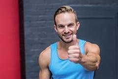 Muskulöser Mann, der oben Daumen gestikuliert Lizenzfreie Stockfotografie