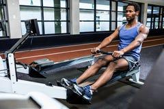Muskulöser Mann, der Rudermaschine verwendet Stockbild