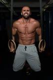Muskulöser Mann-Griff-gymnastische Ringe Lizenzfreie Stockbilder