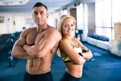 Muskulöser Mann und sportliche Frau, die in der Turnhalle steht Lizenzfreies Stockfoto
