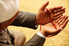 Muslim. Hands with muslim prayer beads stock photography