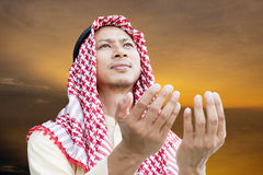 Muslim Arabic man praying. With evening sky background Royalty Free Stock Images