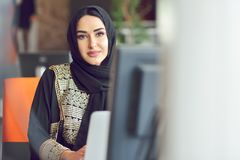 Muslim asian woman working in office with laptop.  royalty free stock photography