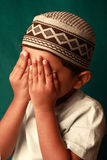 Muslim boy. A Muslim boy with hat praying Stock Image