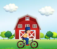 A Muslim boy biking near the barnhouse Stock Images