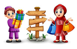 Muslim boy cartoon holding gift box with muslim girl holding shopping bag. Illustration of Muslim boy cartoon holding gift box with Muslim girl holding shopping Stock Images