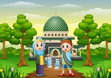 Muslim boy and girl cartoon holding lantern with mosque background Stock Photography