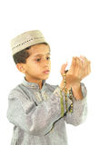Muslim boy praying. Young Muslim boy in traditional ethnic clothing holding prayer beads, white background Stock Photo