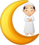 Muslim boy praying on the crescent moon Royalty Free Stock Image