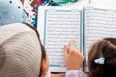 Muslim brother and sister pointing to the word : Ramadan The ho royalty free stock photo