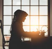 Muslim business people silhouette of islam woman working on office table windows morning flare stock photo