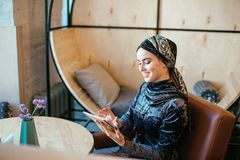 Beautiful Arabic Muslim girl using tablet in cafe. Muslim business woman with beautiful smile holding digital tablet while sitting in cafe Stock Photos