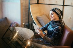 Beautiful Arabic Muslim girl using tablet in cafe. Muslim business woman with beautiful smile holding digital tablet while sitting in cafe Royalty Free Stock Photos