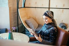 Beautiful Arabic Muslim girl using tablet in cafe. Muslim business woman with beautiful smile holding digital tablet while sitting in cafe Royalty Free Stock Image