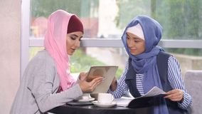 Muslim business woman at a business meeting in a cafe. Muslim business women at a business meeting in a cafe. Woman in hijab holding a tablet computer royalty free stock images