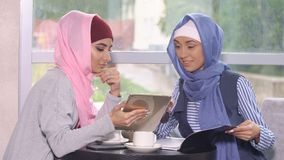 Muslim business woman at a business meeting in a cafe. Muslim business women at a business meeting in a cafe. Woman in hijab holding a tablet computer Stock Images