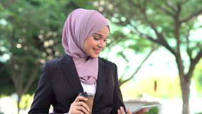 Muslim business woman going to work. Muslim business woman drinking coffee while going to work in morning stock footage
