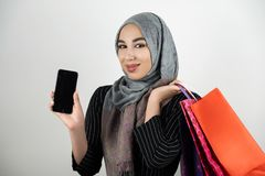 Muslim business woman wearing turban hijab headscarf showing smartphone with one hand and carrying shopping bags in stock photo