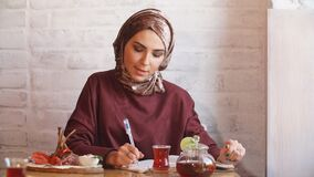 Muslim business woman working documents in cafe. Muslim business woman working documents in cafe stock footage