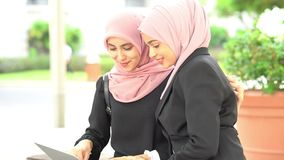 Muslim business women discussing. At outdoor, with laptop stock footage