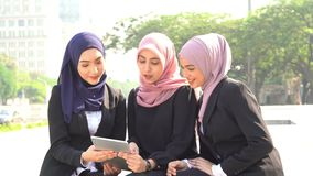 Muslim business women using tablet pc. And laughing together stock video footage