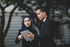 Free Muslim Businessman And Businesswoman Partner Discussing Using Tablet Connection Social Media For Work. Outdoor Setting Stock Photography - 155987102