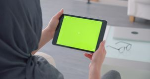 Muslim businesswoman in hijab turns on app on horizontal tablet with green chroma screen and watches attentively. Muslim businesswoman in hijab turns on app on stock footage