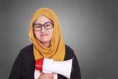 Muslim Businesswoman with Megaphone. Portrait of muslim businesswoman wearing hijab smiling while holding megaphone, leadership motivation marketing advertising Royalty Free Stock Photos